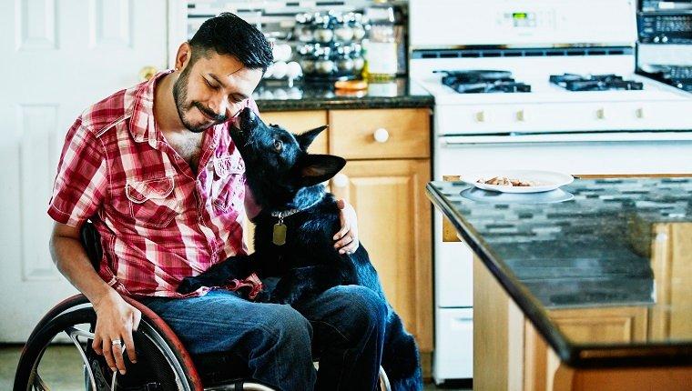 Un homme souriant en fauteuil roulant se fait lécher le visage par un chien alors qu'il traîne dans la cuisine.