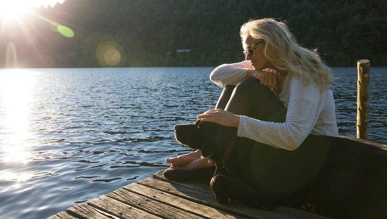 Une femme caresse un chien sur la jetée d'un lac, au lever du soleil.